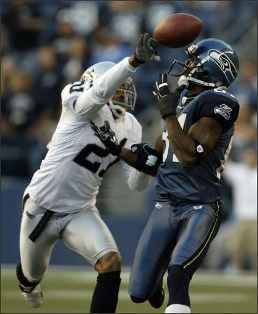 The Seahawks' Nate Burleson (right) has the ball knocked away by Oakland's Nnamdi Asomugha in the first quarter.
