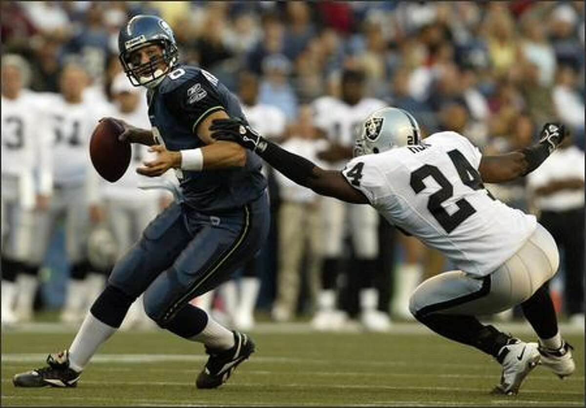Matt Hasselbeck shakes off Oakland's Michael Huff in the first quarter.