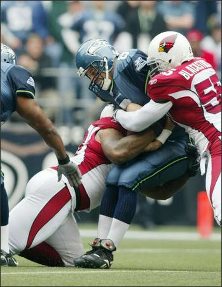 Seahawks quarterback Matt Hasselbeck is sacked for a 10-yard loss by Arizona Cardinals Darnell Dockett, left, during Seattle's first play from scrimmage in the 1st quarter. On right is Cardinals' Darryl Blackstock. Photo: Dan DeLong, Seattle Post-Intelligencer / Seattle Post-Intelligencer