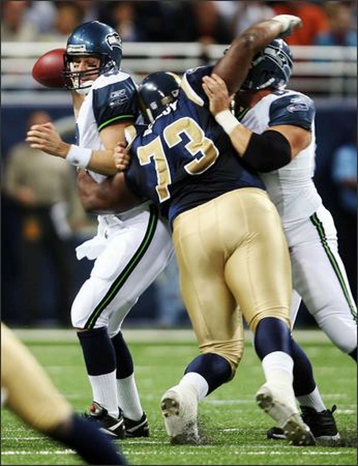 Seahawks Matt Hasselbeck is grabbed by St. Louis Rams Jimmy Kennedy during first quarter action at the Edward Jones Dome in St. Louis.