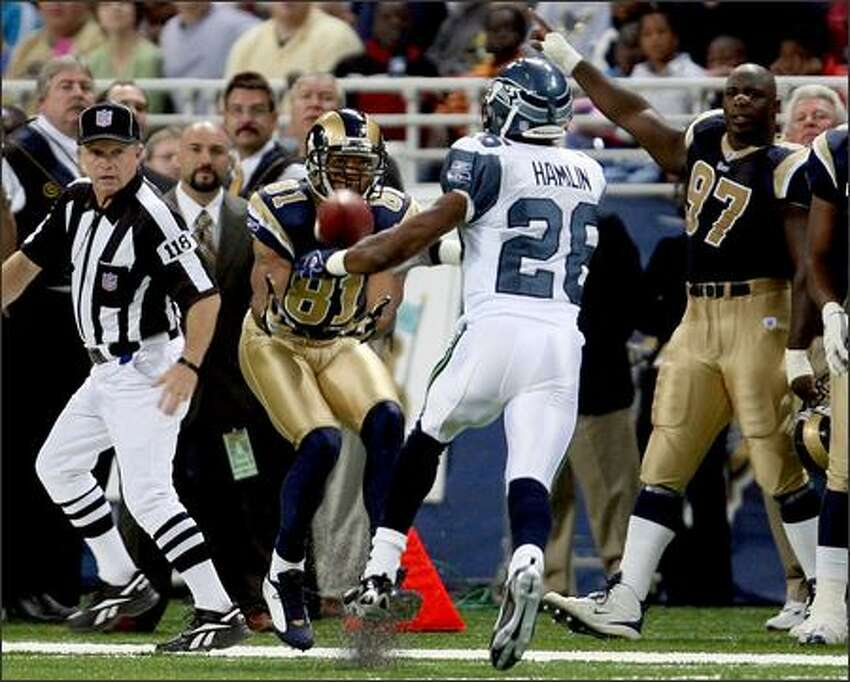 Seahawks Ken Hamlin is unable to disrupt the 38-yard pass to St. Louis Rams Torry Holt during the first play of the game at the Edward Jones Dome in St. Louis.