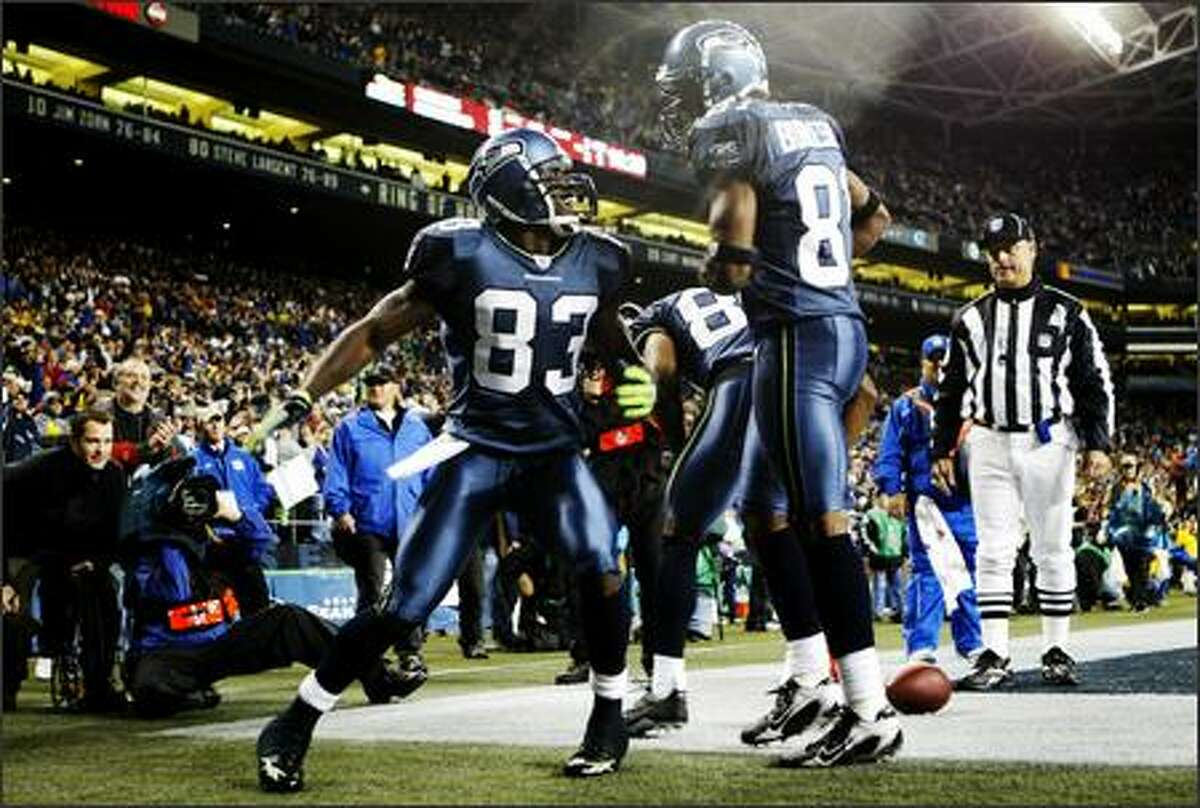 Seahawks player Deion Branch (83) celebrates with Nate Burleson (81) after Branch scored a touchdown against the Oakland Raiders in the first half.