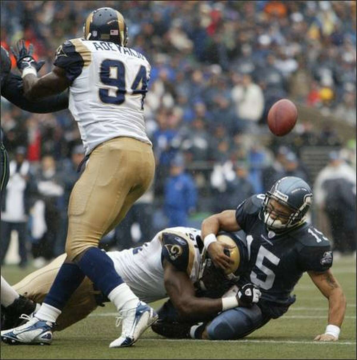 Seahawks quarterback Seneca Wallace fumbles after being sacked by Leonard Little. The play resulted in an 89-yard return by the Rams' Victor Adeyanju (94).