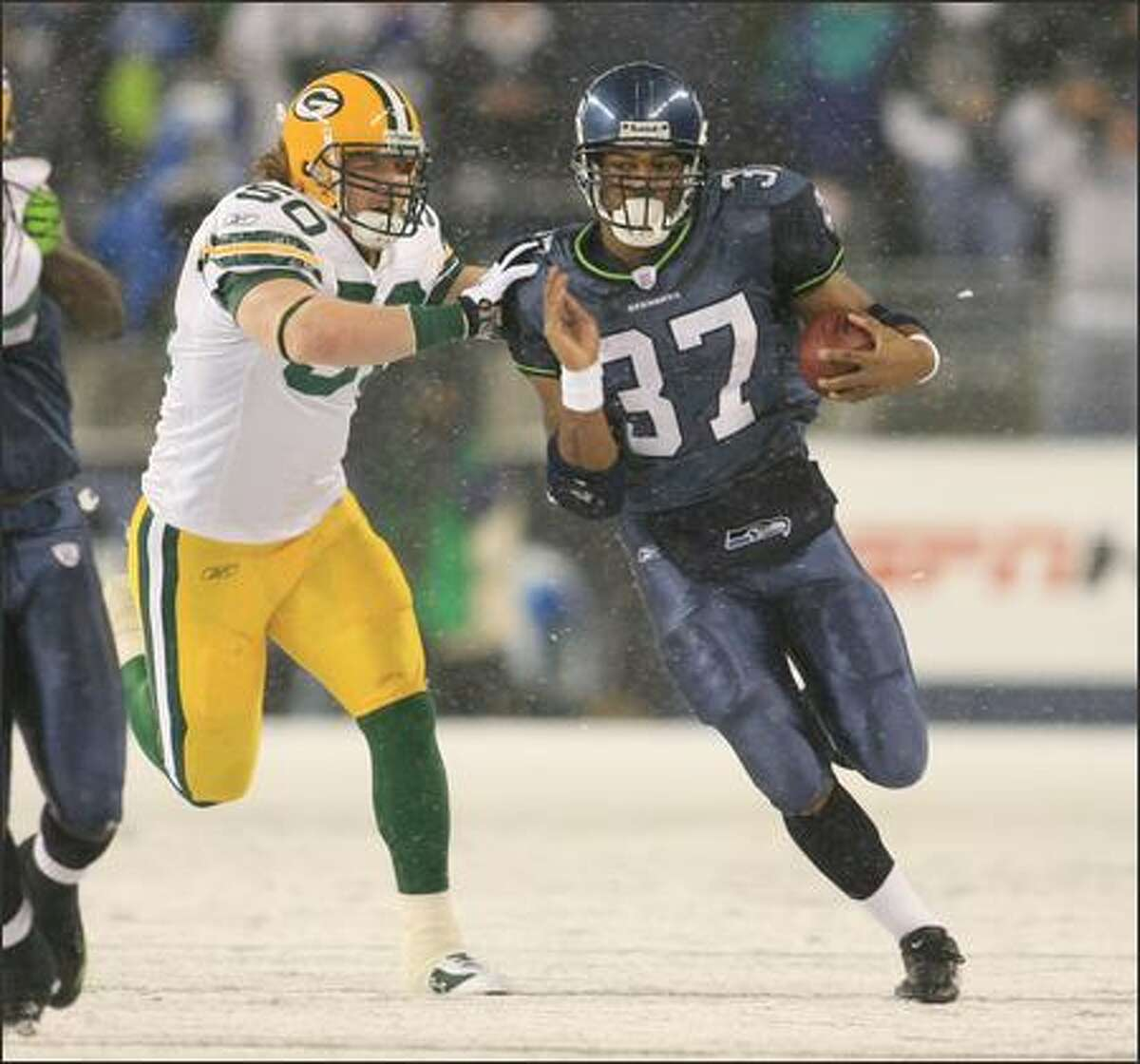 Seattle Seahawks running back Shaun Alexander is pursued by Green Bay Packers linebacker AJ Hawk while running for an 18-yard gain before being pushed out of bounds during first quarter play at Qwest Field in Seattle on Monday.