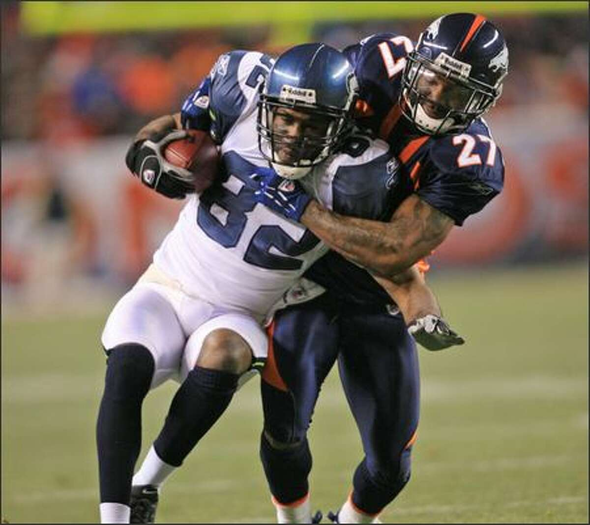 Seahawks wide receiver Darrell Jackson, left, is dragged down by Denver Broncos cornerback Darrent Williams after pulling in a pass for for 7 yards during the first quarter.