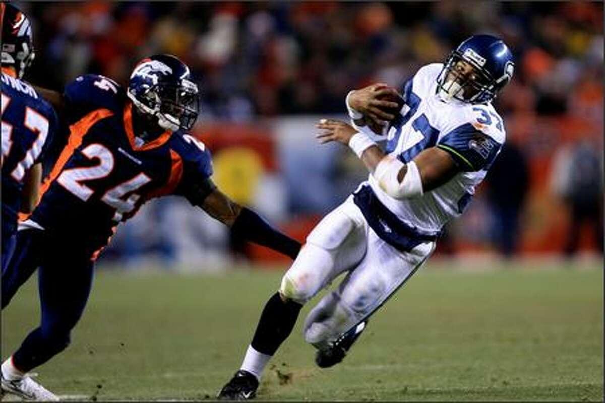 Seahawks running back Shaun Alexander runs for a short gain as Denver Broncos cornerback Champ Bailey defends during the second quarter.