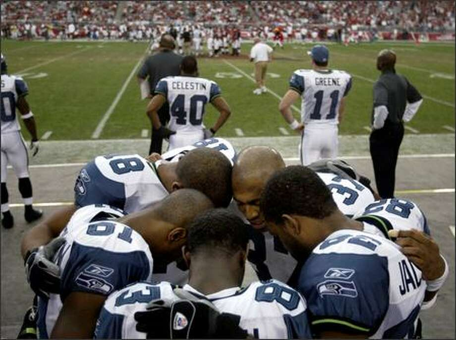 As team captains met at the center of the field, Shaun Alexander leads a pre-game prayer with the receivers -- clockwise, from front: Deion Branch, Nate Burleson, D.J. Hackett, Alexander and Darrell Jackson. In the end, the Seahawks lost to the Arizona Cardinals 27-21. Photo: Scott Eklund, Seattle Post-Intelligencer / Seattle Post-Intelligencer