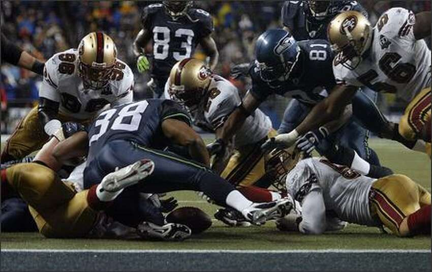 Players from both teams swarm over Shawn Alexander's fumble in the first quarter. Seahawks' Nate Burleson finally came up with the ball.