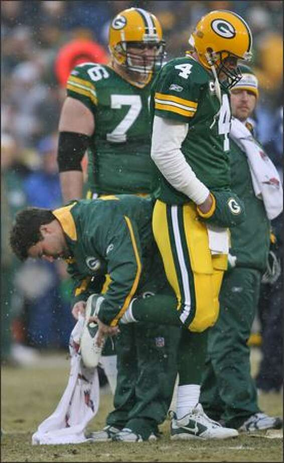 Packers quarterback Brett Favre has his cleats cleaned during first-quarter action. Photo: Mike Urban, Seattle Post-Intelligencer / Seattle Post-Intelligencer