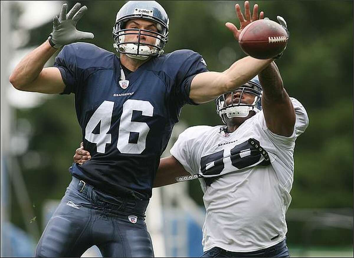 Seahawks linebacker Leroy Hill knocks away a pass intended for tight end Joe Newton (46) during Seahawks training camp.