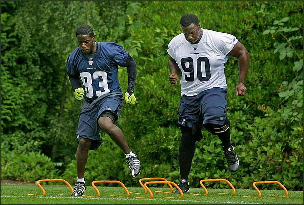 Seahawks receiver Deion Branch (83) and defensive tackle Marcus Tubb (90) work on agility drills.