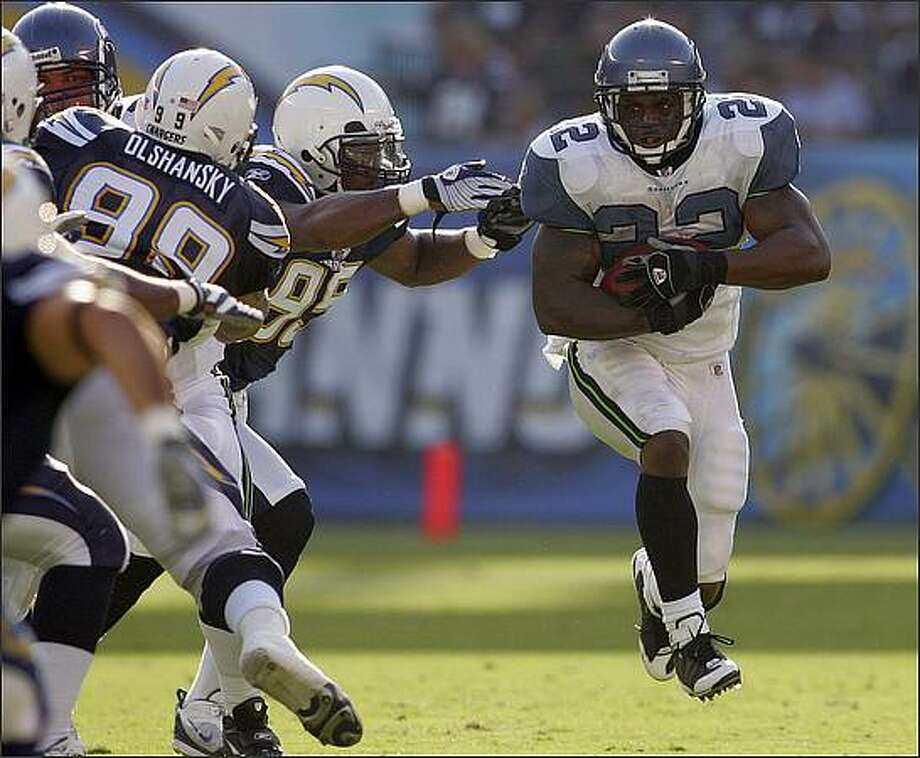 Seattle Seahawks running back Julius Jones, right, breaks away from the line for a 4-yard run during the first quarter of Monday's preseason game against the San Diego Chargers in San Diego. Defending are Igor Olshansky (99) and Shaun Phillips (95). (AP Photo/Chris Park)