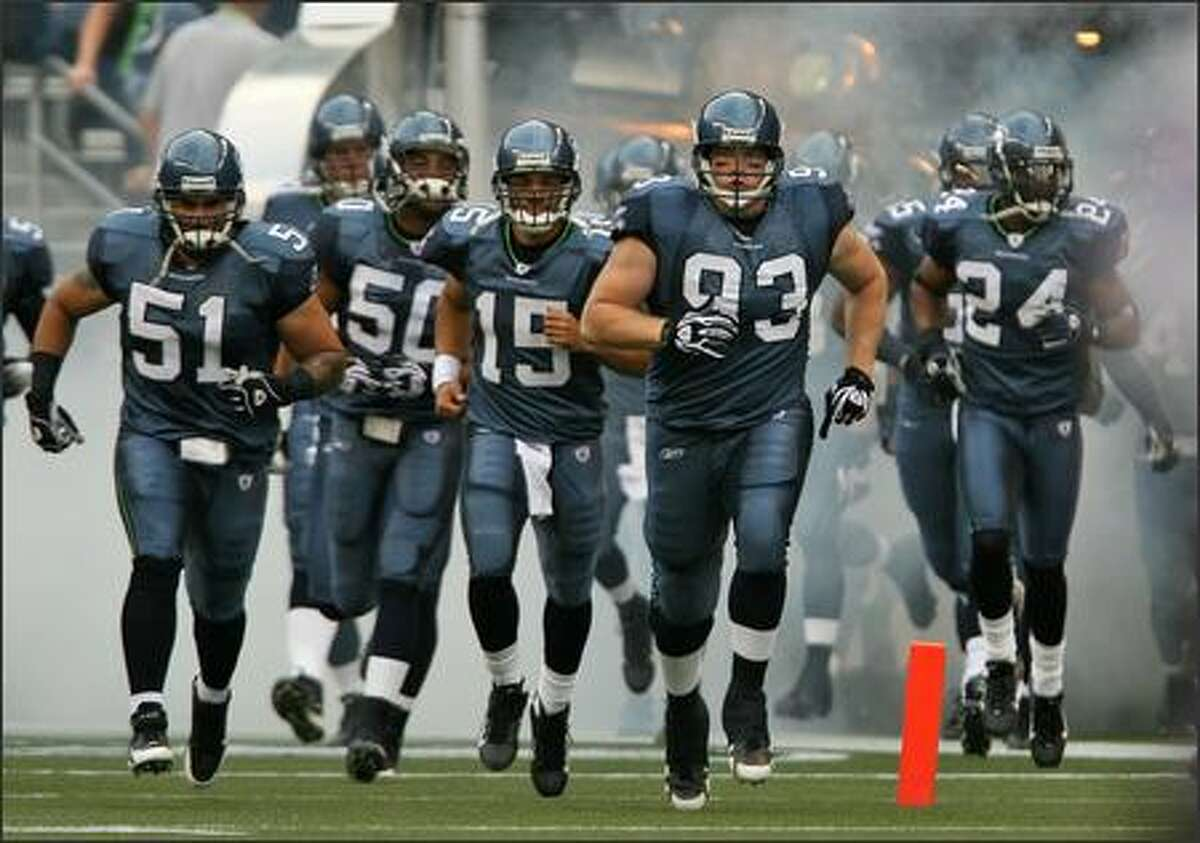 Seattle Seahawks Lofa Tatupu (51), Lance Laury (50), Seneca Wallace (15), Craig Terrill (93) and Deon Grant (24) take the field to face the Minnesota Vikings at Qwest Field in Seattle, Wash., Saturday August 24, 2007.