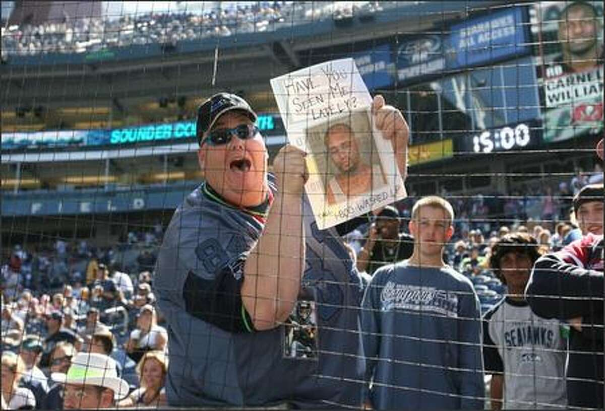 Lorin Sandretzky, of Seattle, holds up a picture showing the booking photo of Jerramy Stevens prior to the start of game in which the Seattle Seahawks beat the Tampa Bay Buccaneers 20-6 at Qwest Field.