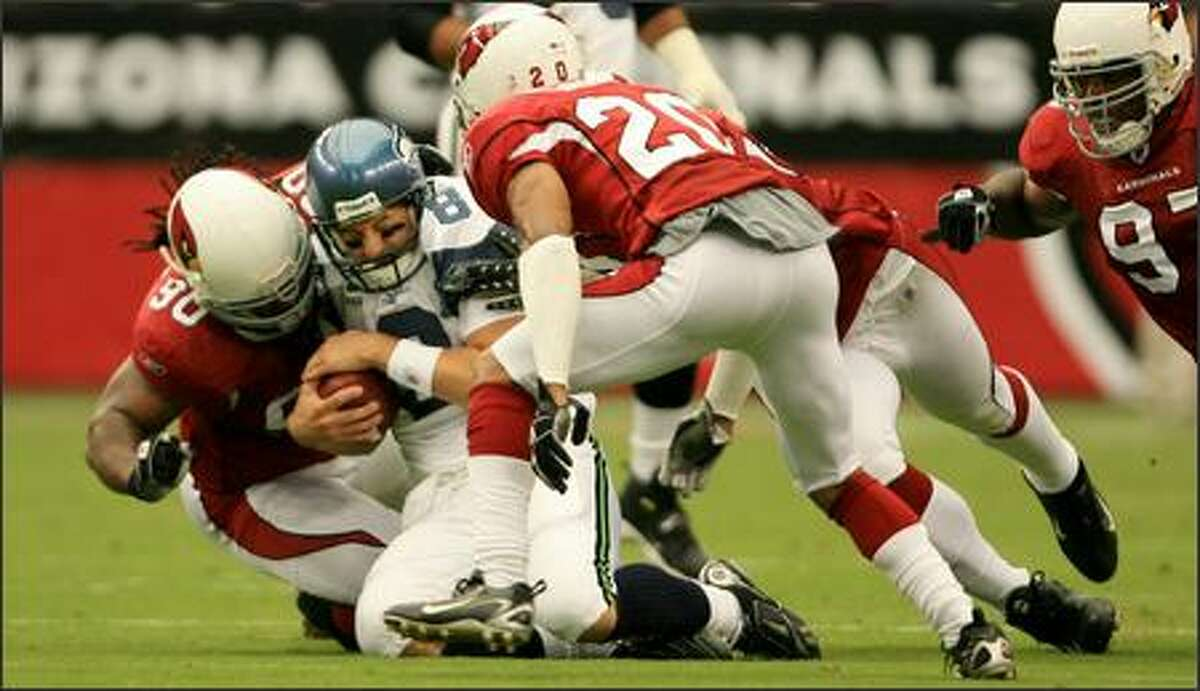 Seattle Seahawks quarterback Matt Hasselbeck is hit by defensive tackle Darnell Dockett after scrambling for 6 yards in the 1st quarter.