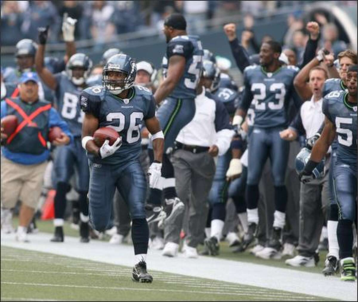 As his Seahawks teammates on the sideline become happy spectators, Josh Wilson returns the opening kickoff 72 yards.