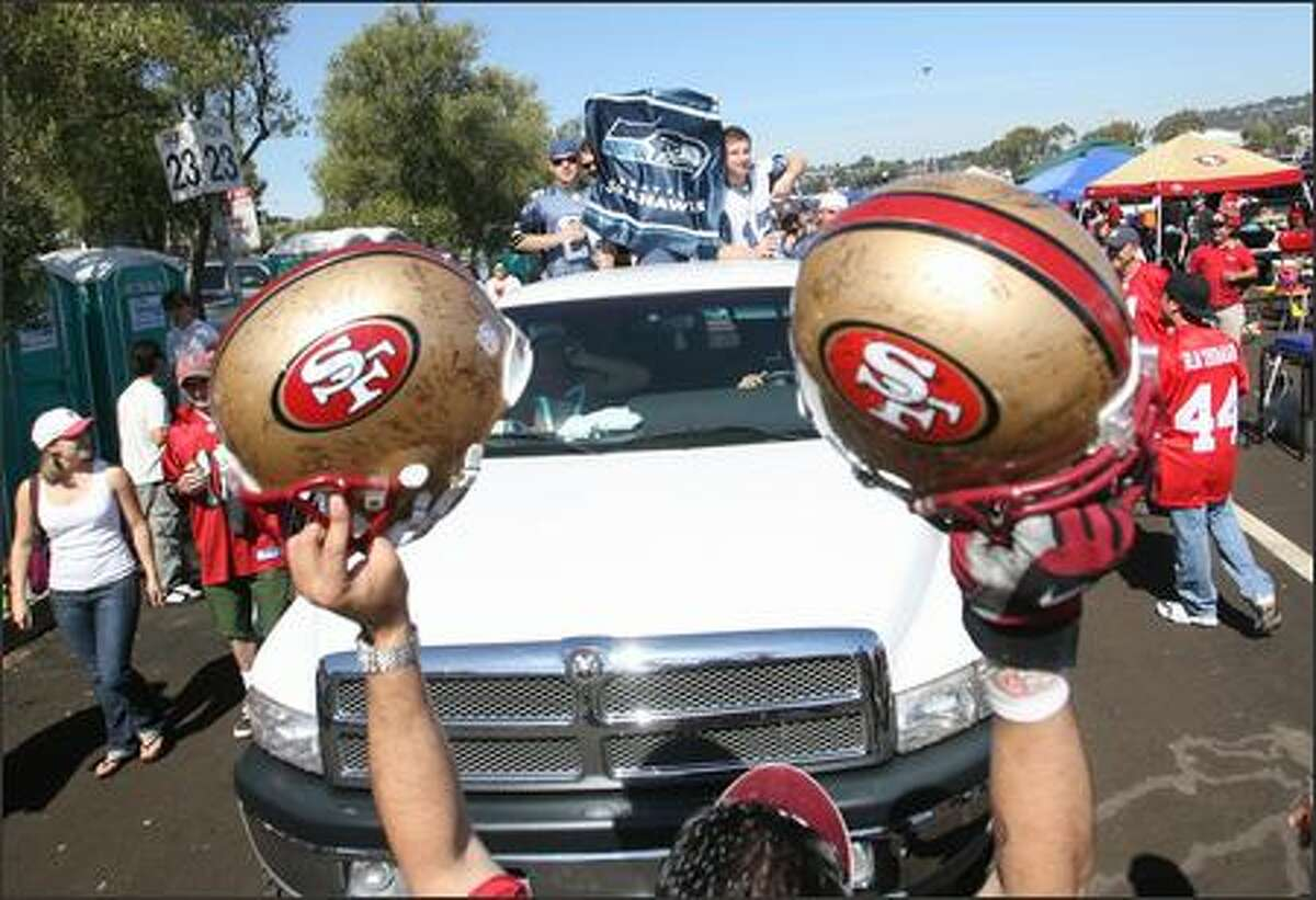 A 49ers fan holds up two helmets and stands in the way of a truck carrying a load of Seahawks fans prior to the start of the game.