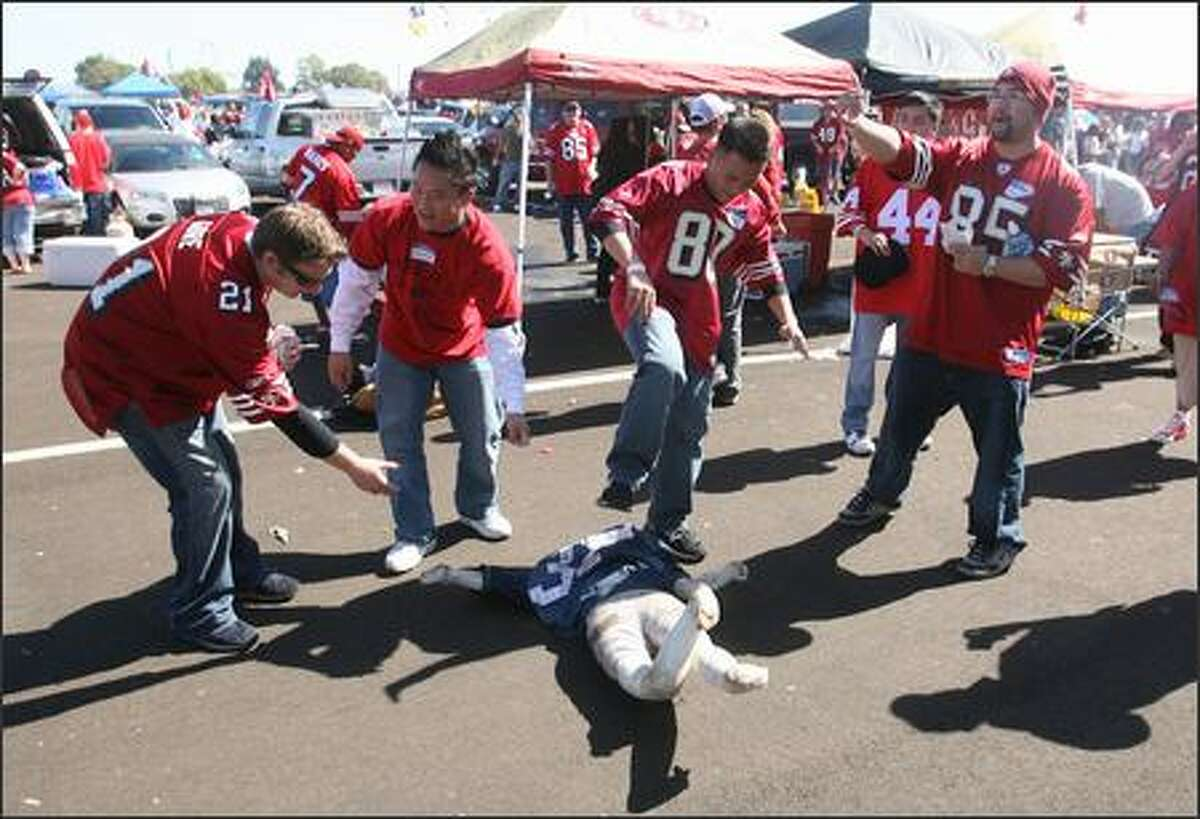 49ers fans beat a doll on the ground wearing a Shaun Alexander jersey prior to the start of the game.