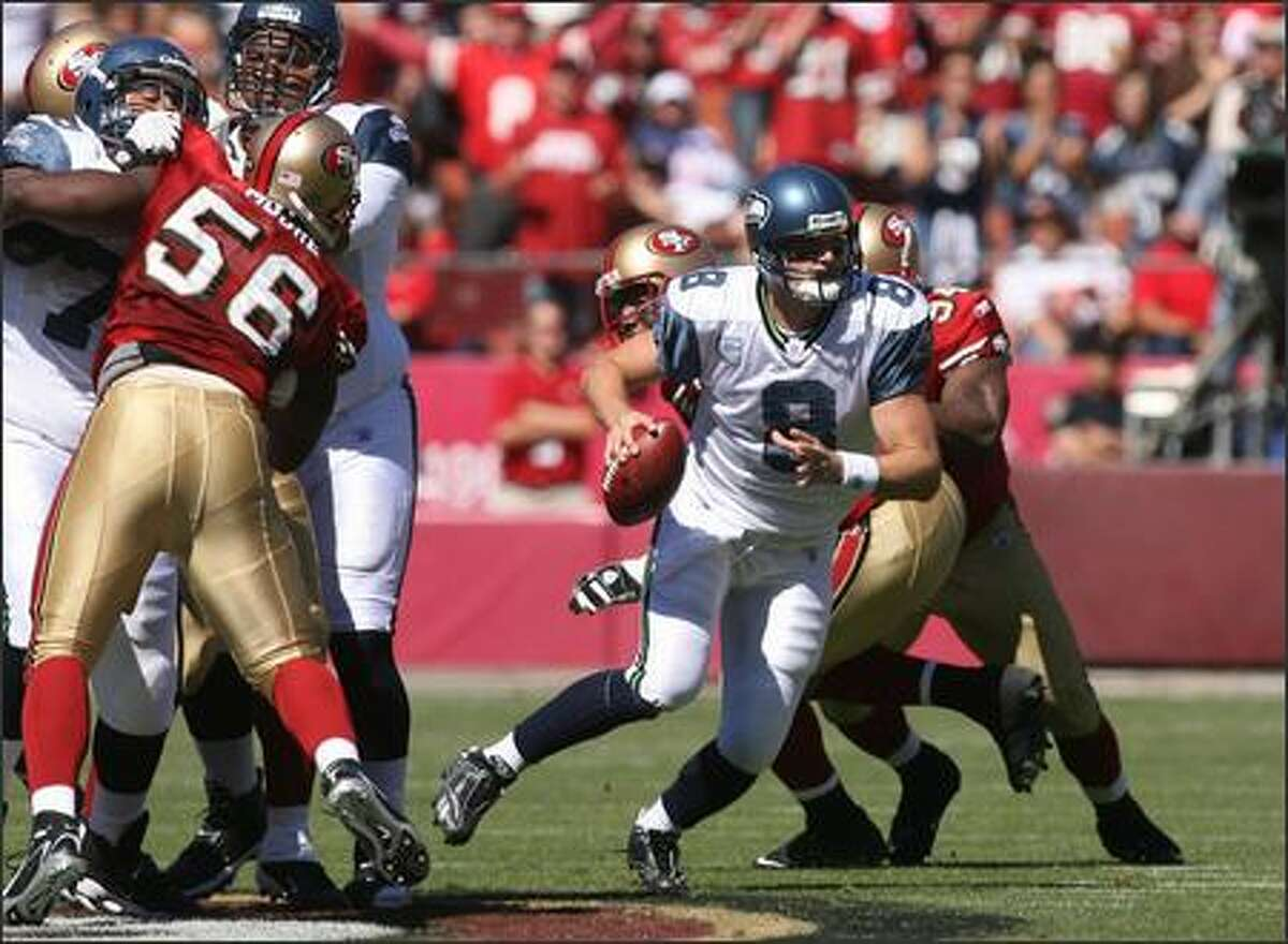 Matt Hasselbeck looks down field as he rolls out of the pocket in the first quarter of the Seattle's game against the San Francisco.