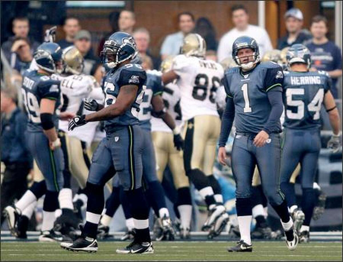 Punter Ryan Plackemeier walks back to the sidelines after fumbling a snap, allowing New Orleans to score a touchdown.