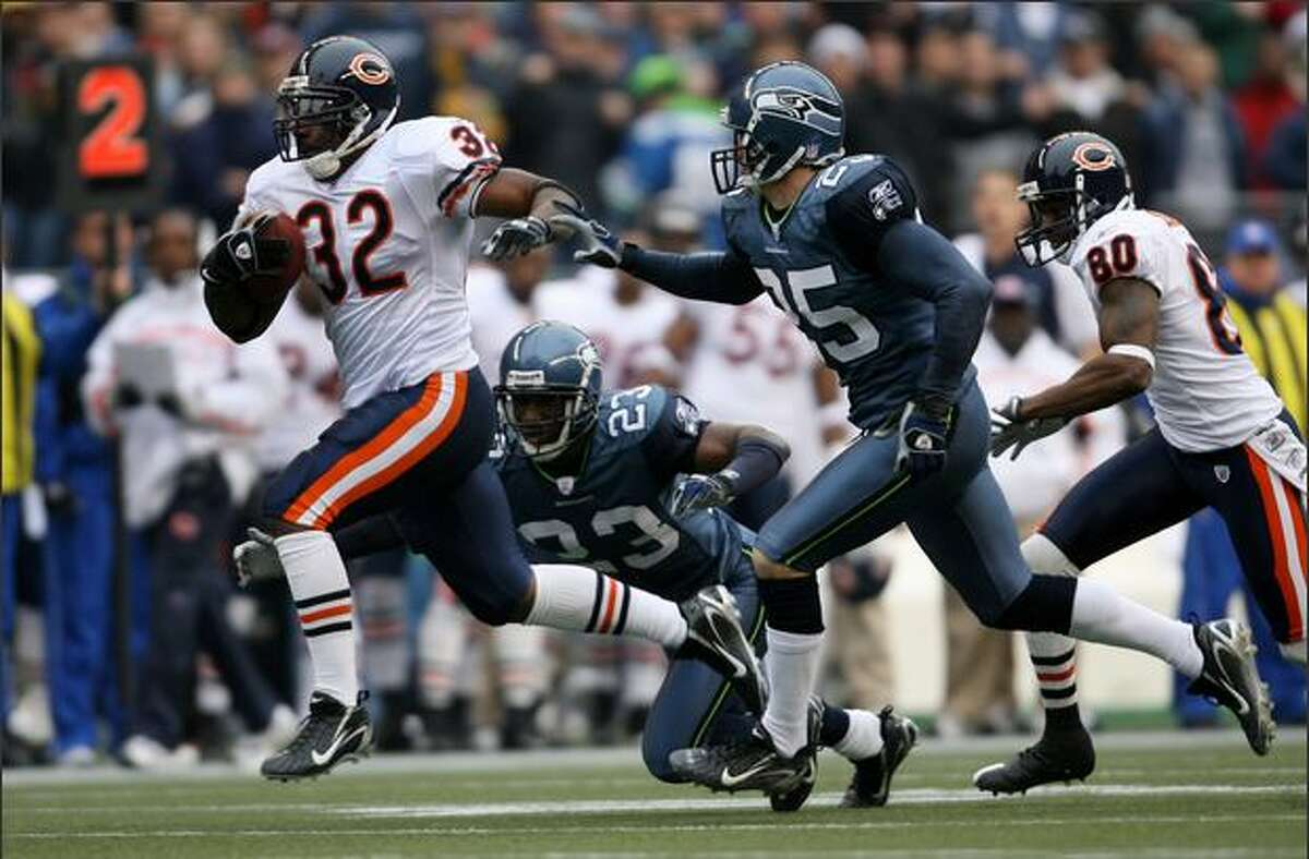 Chicago Bears running back Cedric Benson runs for a 43-yard touchdown, as Seattle's Marcus Trufant and Brian Russell pursue on the second play from scrimmage in the 1st quarter.