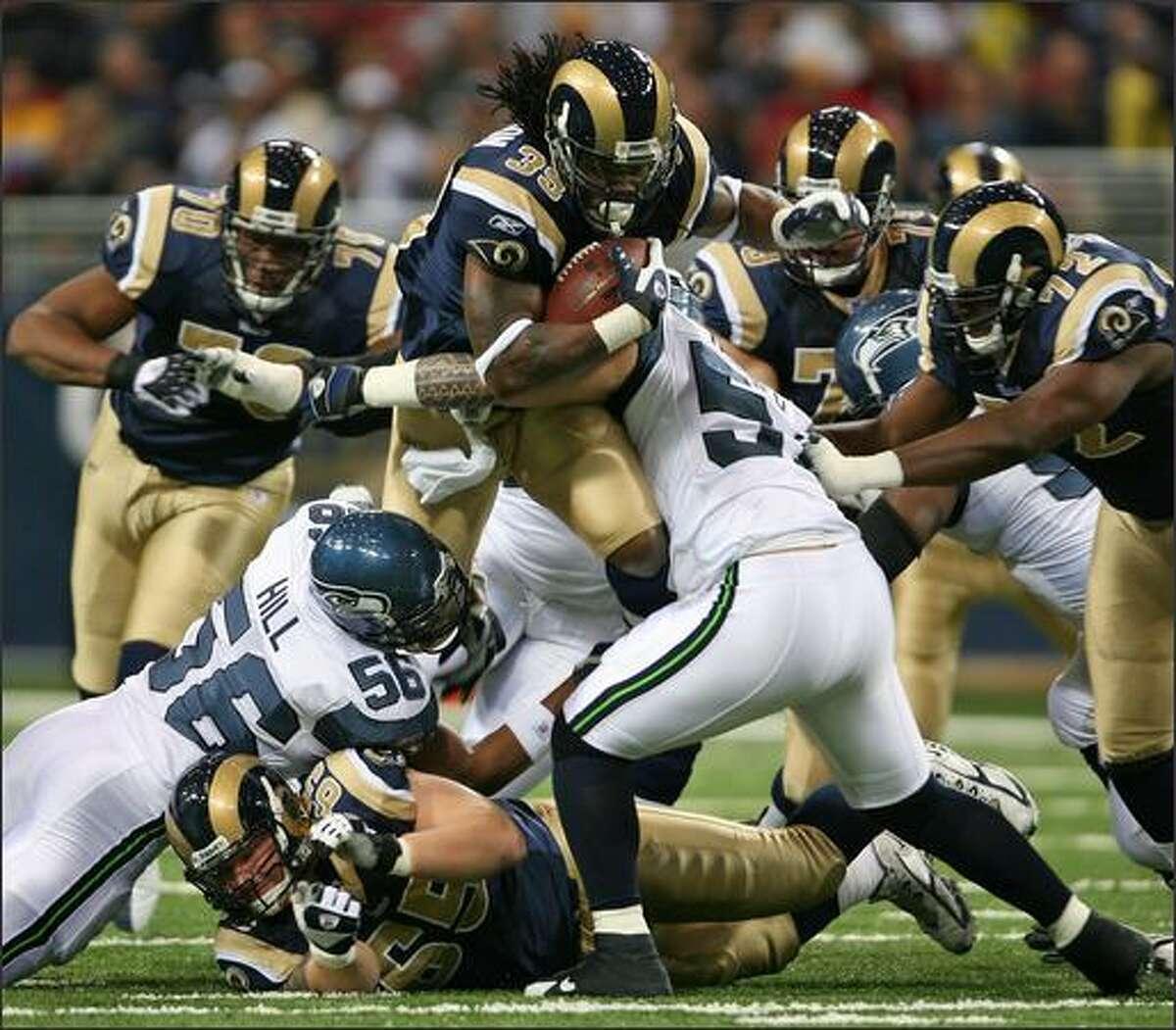 Seattle Seahawks linebacker LeRoy Hill (56) and linebacker Lofa Tatupu (51) get a grip on St. Louis Rams running back Steven Jackson during the first quarter.