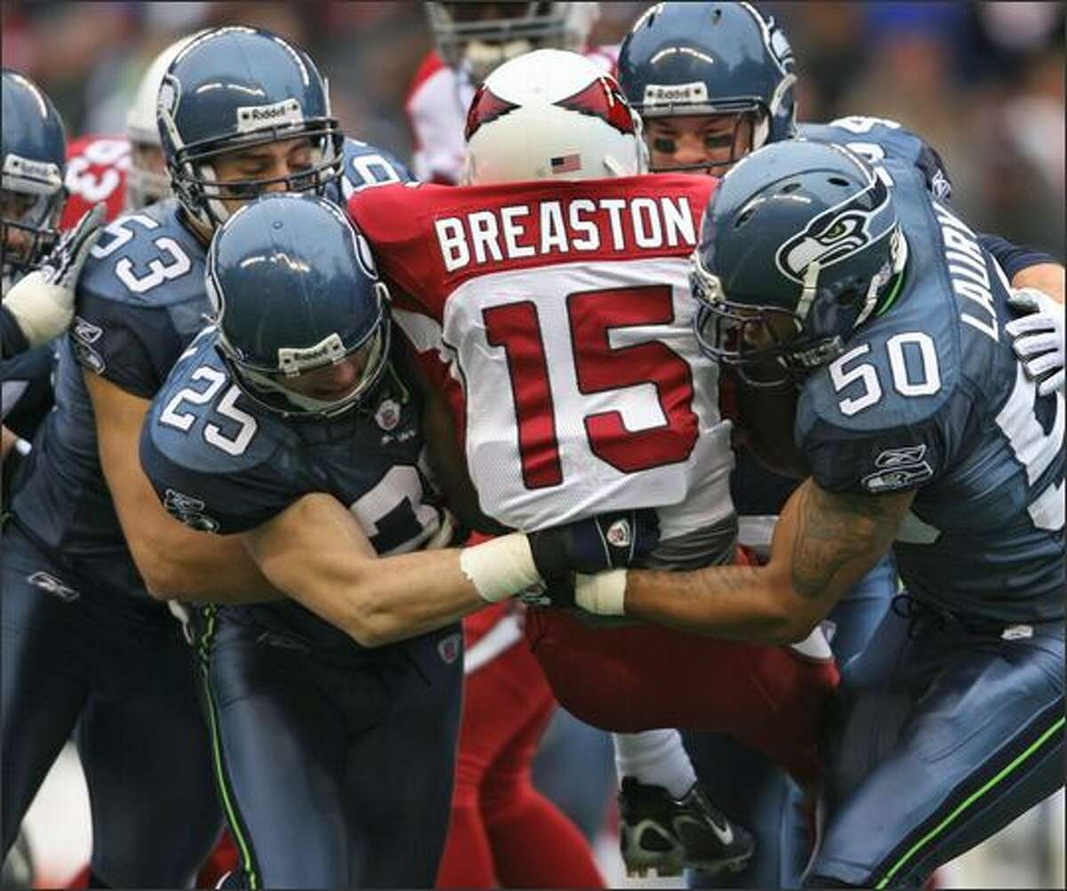 Arizona Cardinals Steve Breaston is sandwiched by Seahawks players (clockwise from bottom left) Brian Russell, Niko Koutouvides, Will Herring and Lance Laury as he returns the opening kickoff.