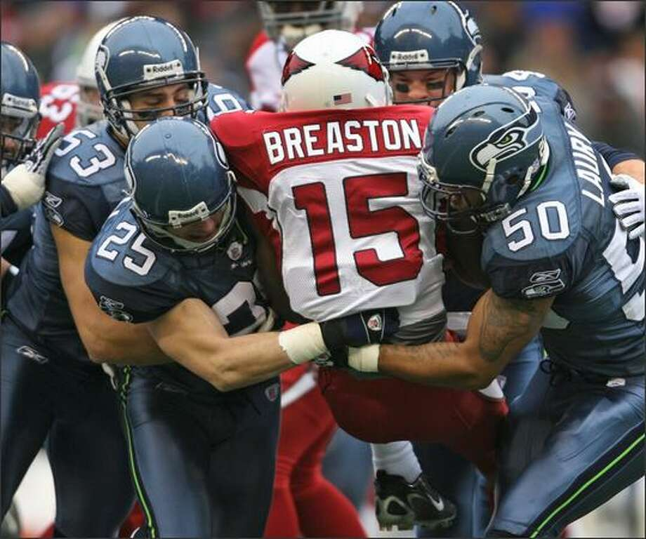 Arizona Cardinals Steve Breaston is sandwiched by Seahawks players (clockwise from bottom left) Brian Russell, Niko Koutouvides, Will Herring and Lance Laury as he returns the opening kickoff. Photo: Dan DeLong, Seattle Post-Intelligencer / Seattle Post-Intelligencer
