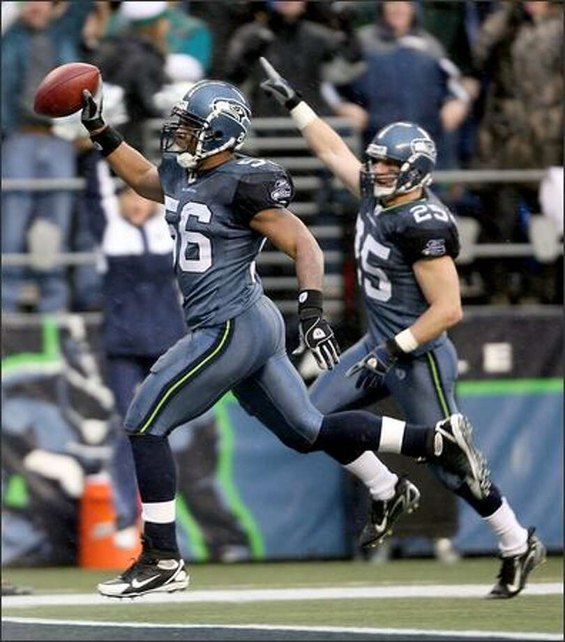 Leroy Hill crosses the goal line after scooping up a fumble and rumbling 20-yards for a touchdown as Brian Russell follows him in as the Seattle Seahawks beat the Baltimore Ravens 27-6 at Qwest Field. Photo: Scott Eklund, Seattle Post-Intelligencer / Seattle Post-Intelligencer