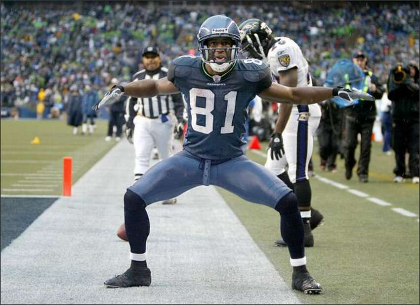 Nate Burleson reacts after catching the first touchdown pass in the second quarter for 21-yards as Raven's safety Ed Reed walks off dejected as the Seattle Seahawks beat the Baltimore Ravens 27-6 at Qwest Field.
