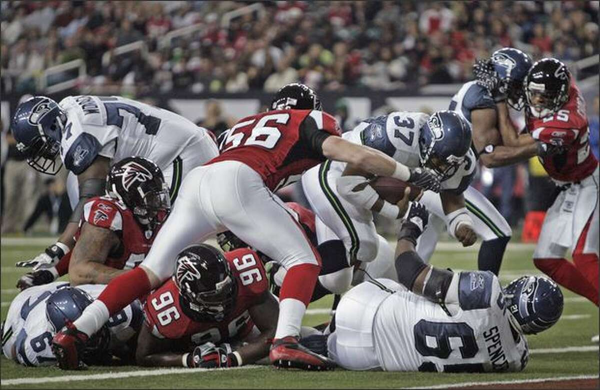 Seattle Seahawks running back Shaun Alexander breaks through the line for a touchdown as Atlanta Falcons linebacker Keith Brooking closes in during the first quarter.