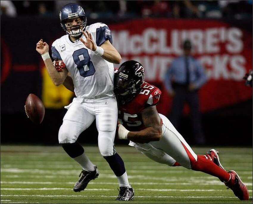 Seattle Seahawks' quarterback Matt Hasselbeck fumbles the ball after being tackled by Atlanta Falcons' John Abraham.
