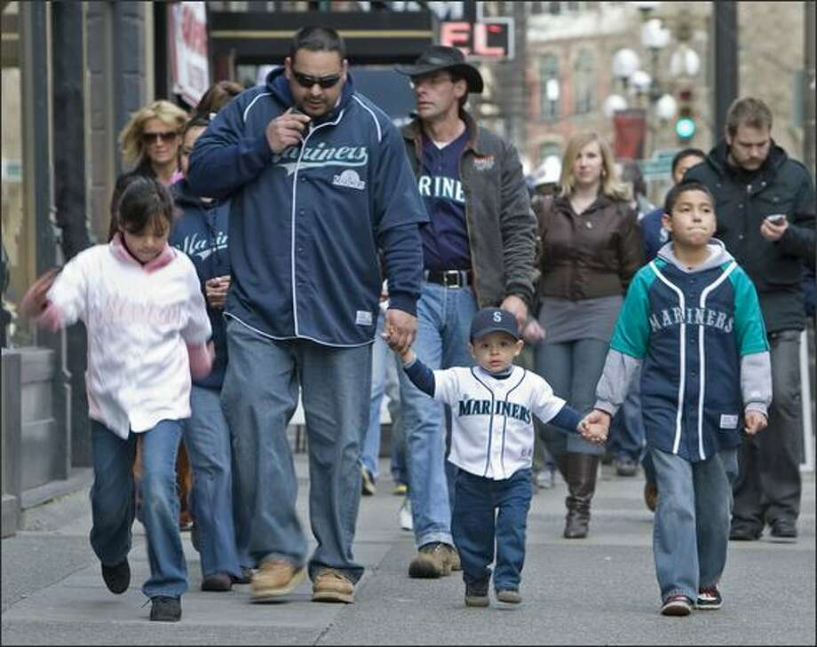 Walking down First Avenue towards Safeco field, taking Antonio Lopez, 22 months, to his first Mariners game, are from the left: His sister, Kimberly, 7; his dad, Antonio Sr, his brother Adrian, 9. Mom, Elizabeth, is just behind her husband. Photo: Grant M. Haller, Seattle Post-Intelligencer / Seattle Post-Intelligencer
