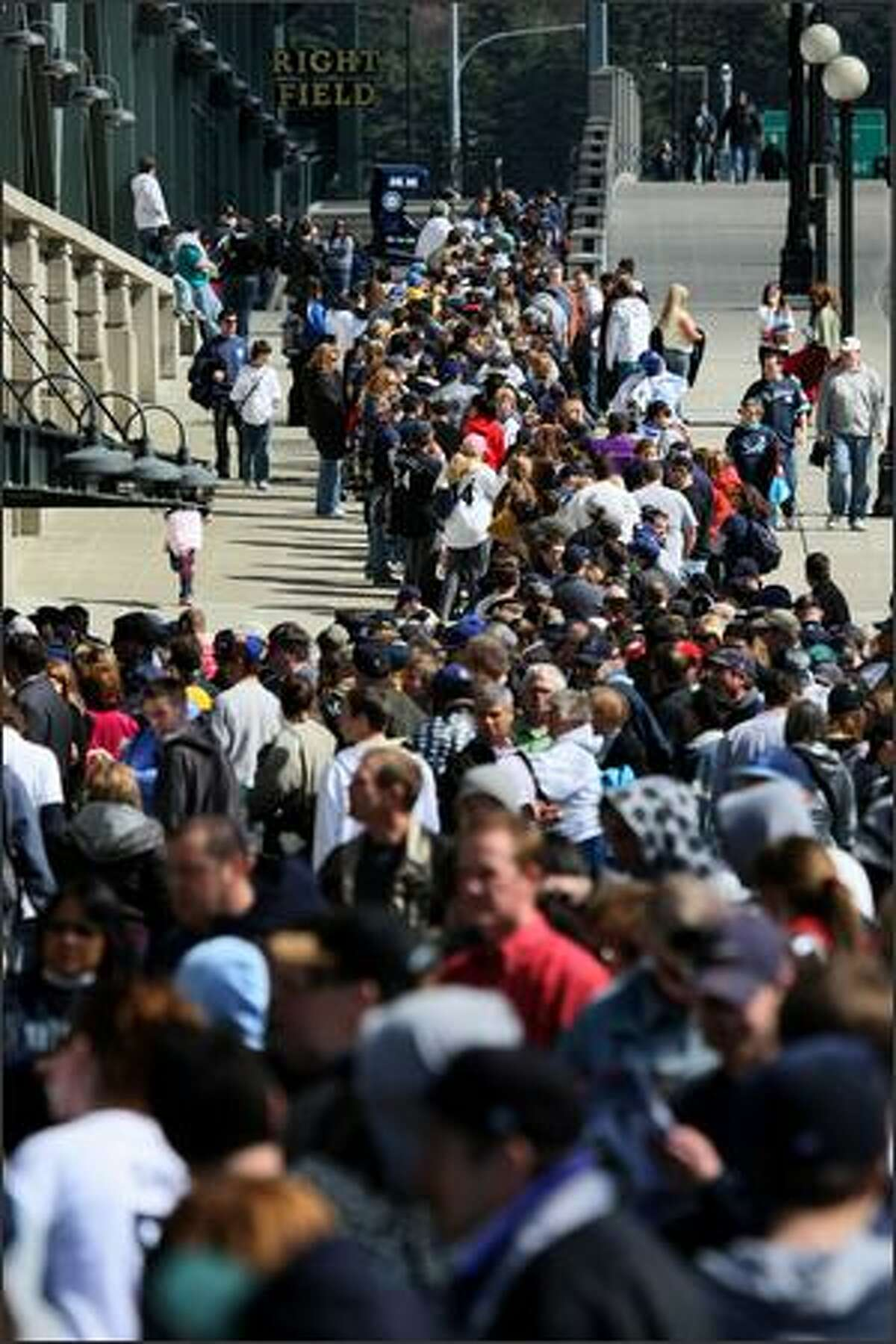 Fans line up to get into Safeco Field during the Seattle Mariners season opener at Safeco in Seattle.