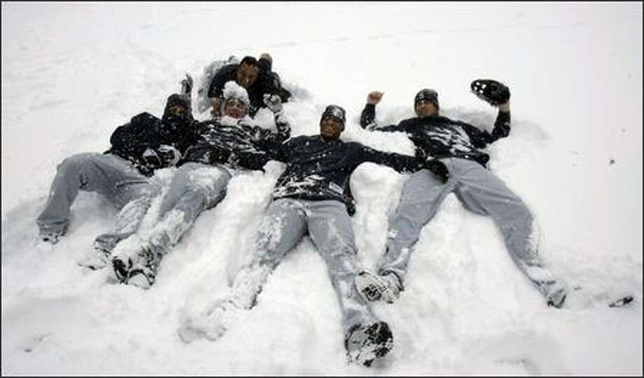 Third base coach Carlos Garcia, top, supervises as, from left, Jose Vidro, Jose Lopez, Adrian Beltre and Richie Sexson play in the snow.  For the second day in a row, a scheduled Mariners-Indians doubleheader was postponed because of snow in Cleveland. Photo: Associated Press / Associated Press
