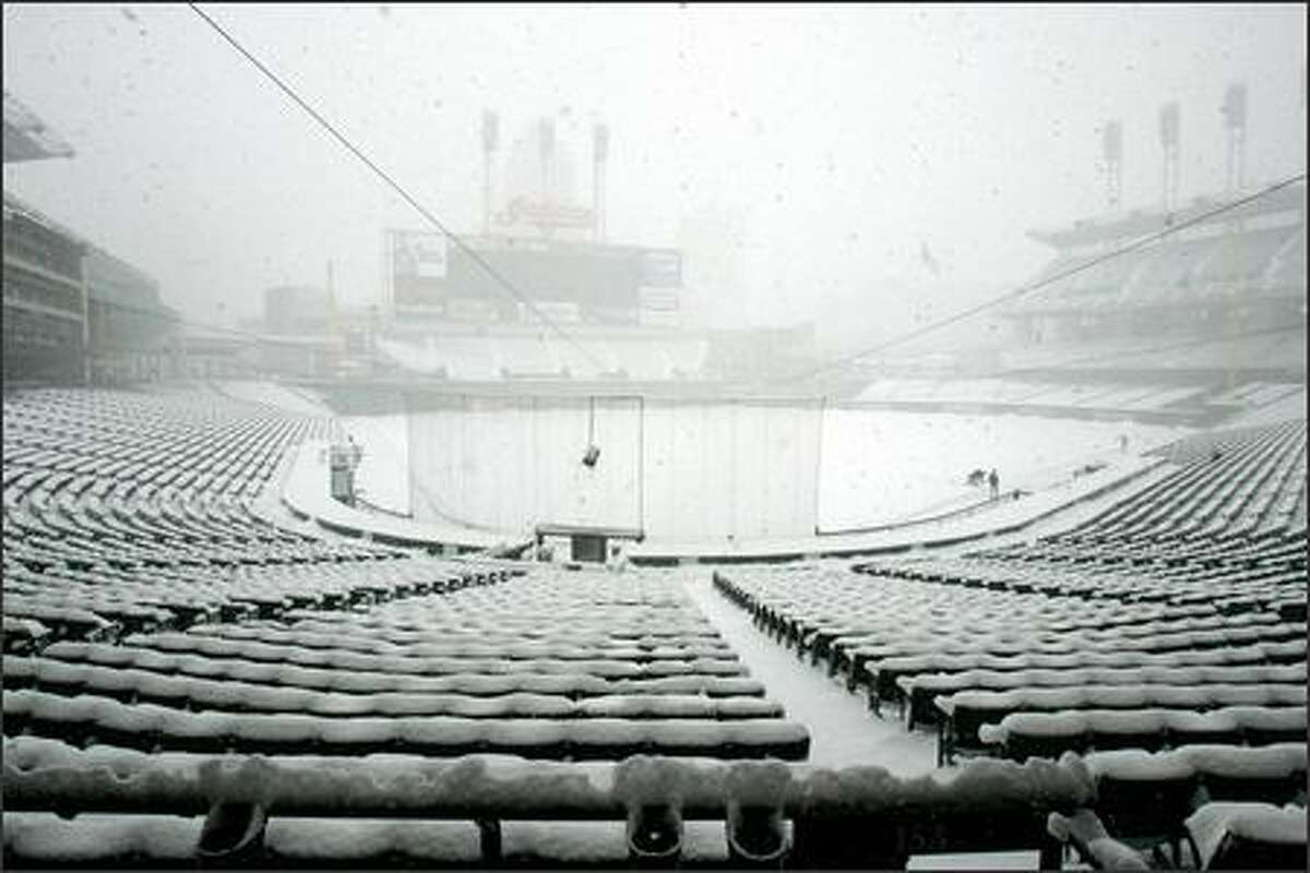 Jacobs Field in Cleveland is empty except for a few Mariners playing in the snow. Snow continued to fall throughout the day Sunday.