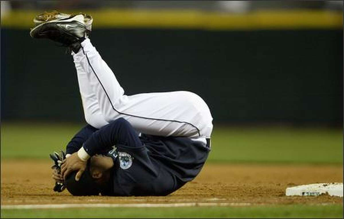 Seattle catcher Kenji Johjima rolls on his back and holds his head in disbelief after being doubled off first on a line drive into a double play by Yuniesky Betancourt in the second inning.