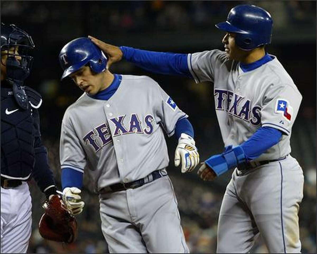 Texas' Jerry Hairston, right, slaps the helmet of teammate Ian Kinsler after Kinsler hit a two-run homer off of Seattle starter Jarrod Washburn in the fifth inning.