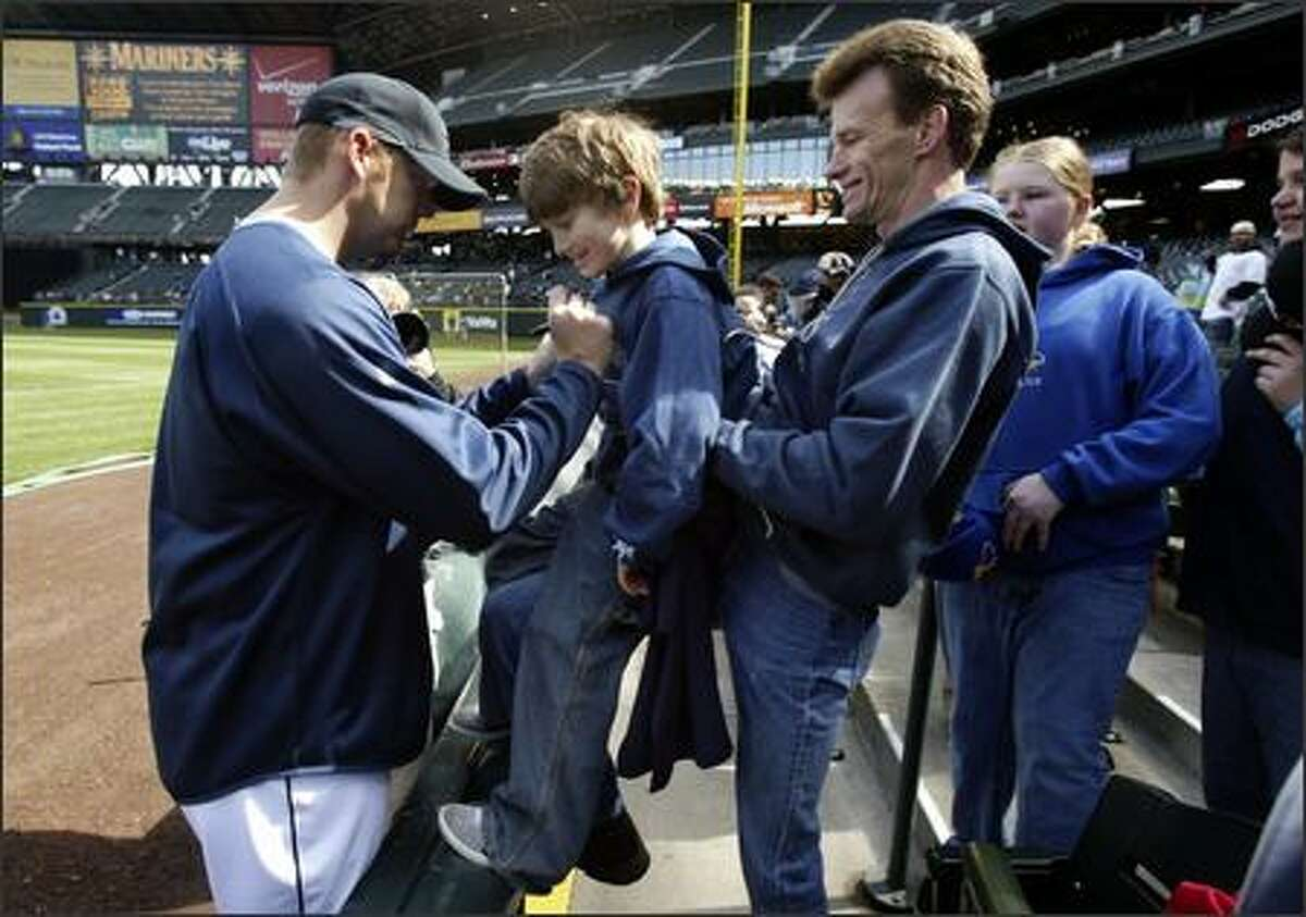 Stacey Brown lifts up his son Dakota Gabler-Brown, 6, so that Seattle Mariners pitcher J.J. Putz can sign his T-shirt prior to the game. J.J. Putz t-shirts were given away to fans at Safeco Field.