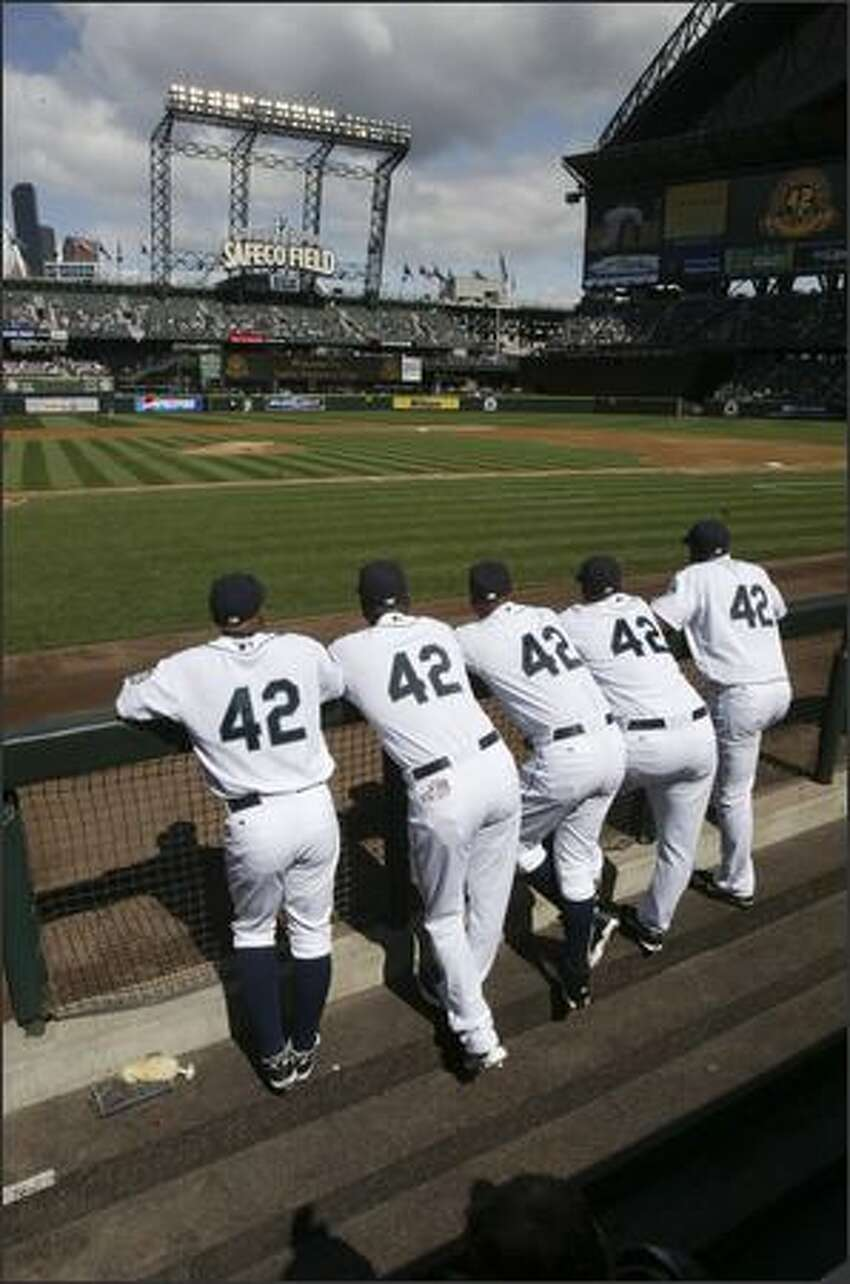 Mariners players -- from left to right -- Jason Ellison, Arthur Rhodes, Miguel Batista, Jose Lopez and Adrian Beltre line up in the dugout and watch a video tribute to Jackie Robinson as part of a ceremony commemorating the 60th anniversary of his breaking the color barrier in major league baseball. A number of Mariners and Rangers players wore Robinson's number 42 during the game.