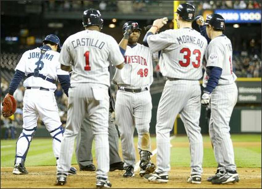 Minnesota Twins players gather at home plate after Torii Hunter hit a grand slam driving in Luis Castillo, Justin Morneau (33) and Jason Tyner (12) on Tuesday at Safeco Field during the fifth inning in Seattle.