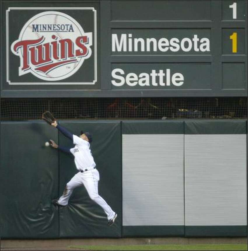 Seattle Mariners player Raul Ibanez can't get to a deep left field hit from Michael Cuddyer fast enough against the Minnesota Twins on Tuesday at Safeco Field during the first inning in Seattle. The play drove in Joe Mauer for a run.