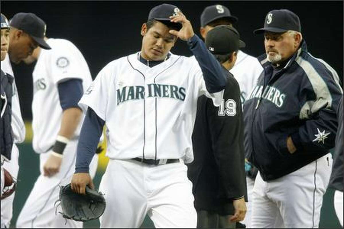 Felix Hernandez leaves the mound with a strained elbow as manager Mike Hargrove (right) looks on