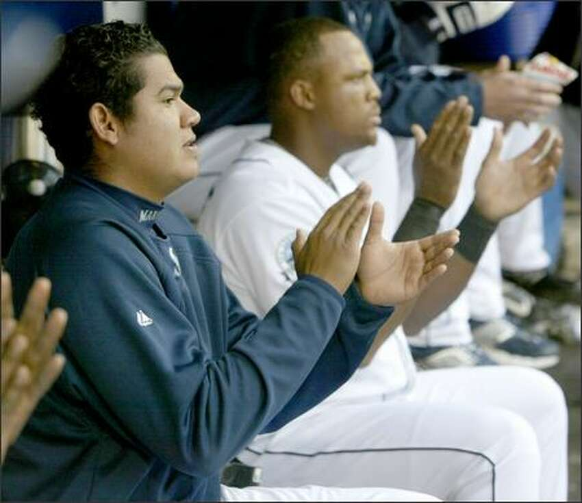 Felix Hernandez, left, applauds as Yuniesky Betancourt hits a home run in the third inning.