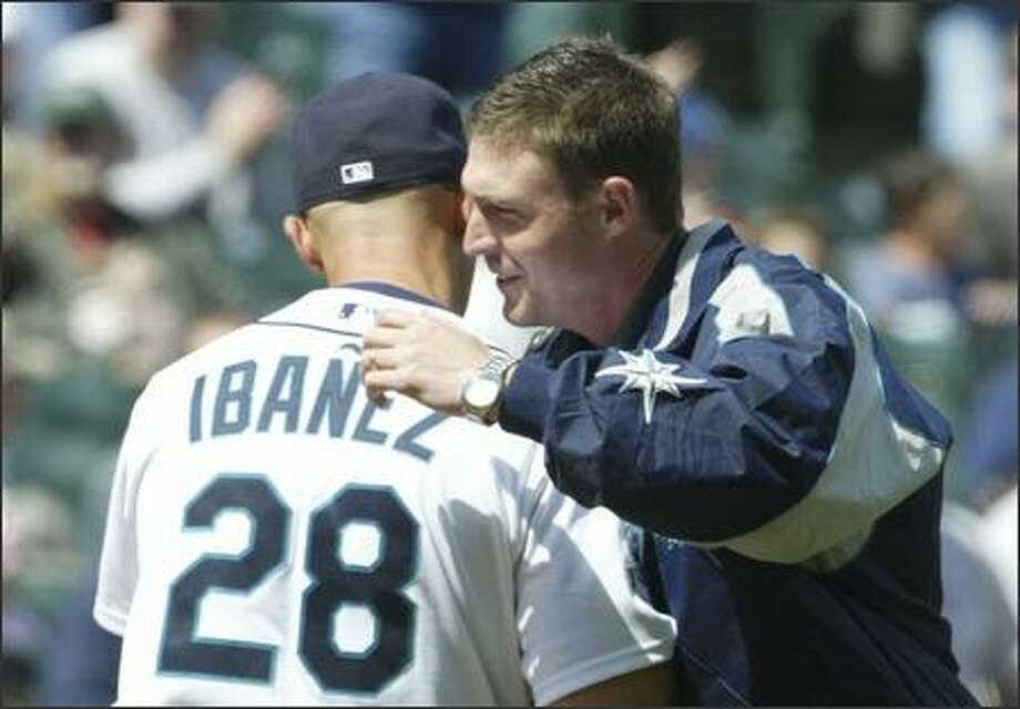 Former Seattle Mariners catcher Dan Wilson gives Raul Ibanez a hug after throwing out the ceremonial first pitch against the Kansas City Royals at Safeco Field Sunday. Photo: Andy Rogers, Seattle Post-Intelligencer / Seattle Post-Intelligencer