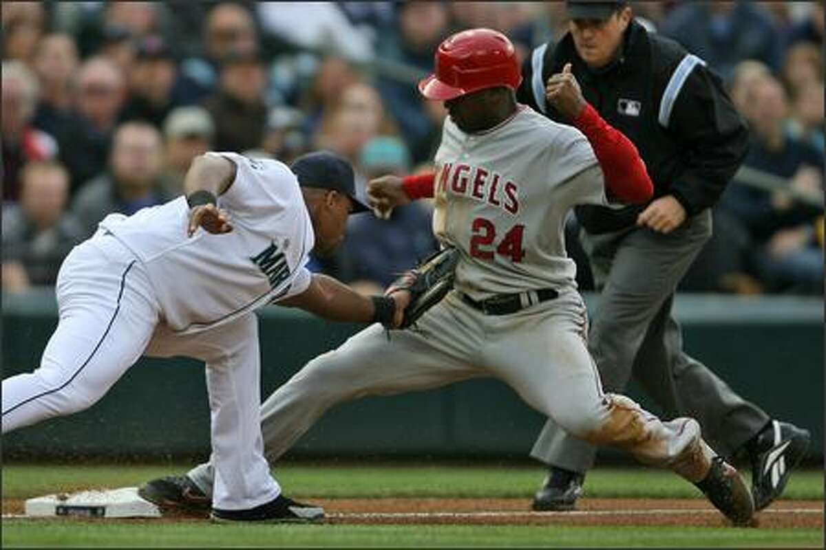 Adrian Beltre (left) is unable to make the tag on Los Angeles' Gary Matthews, who took third base on a single by Casey Kotchman in the first inning.