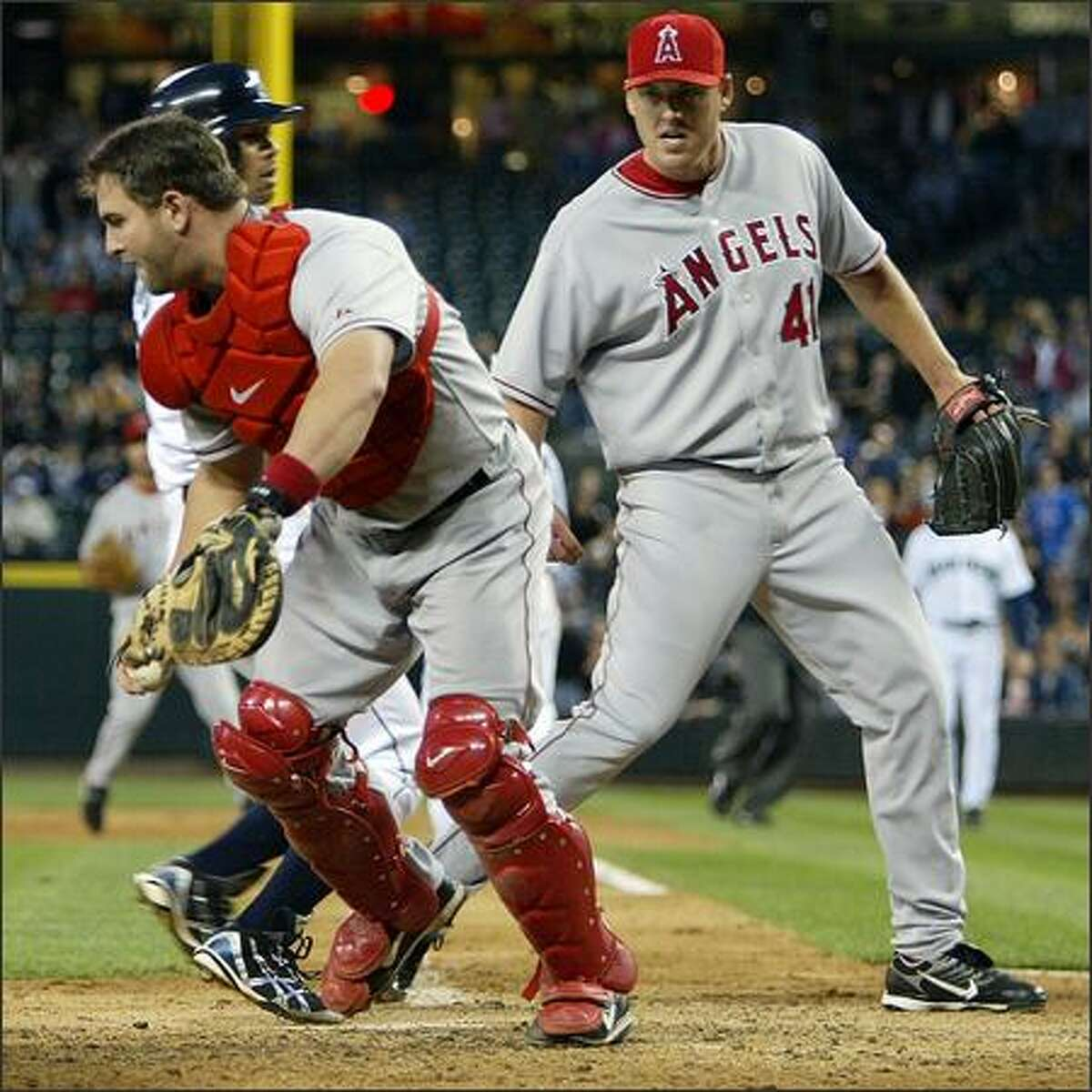 Jose Lopez is forced out at home by Angels catcher Mike Napoli on a bases-loaded fielder's choice by Richie Sexson as pitcher John Lackey backs him up in the sixth inning.