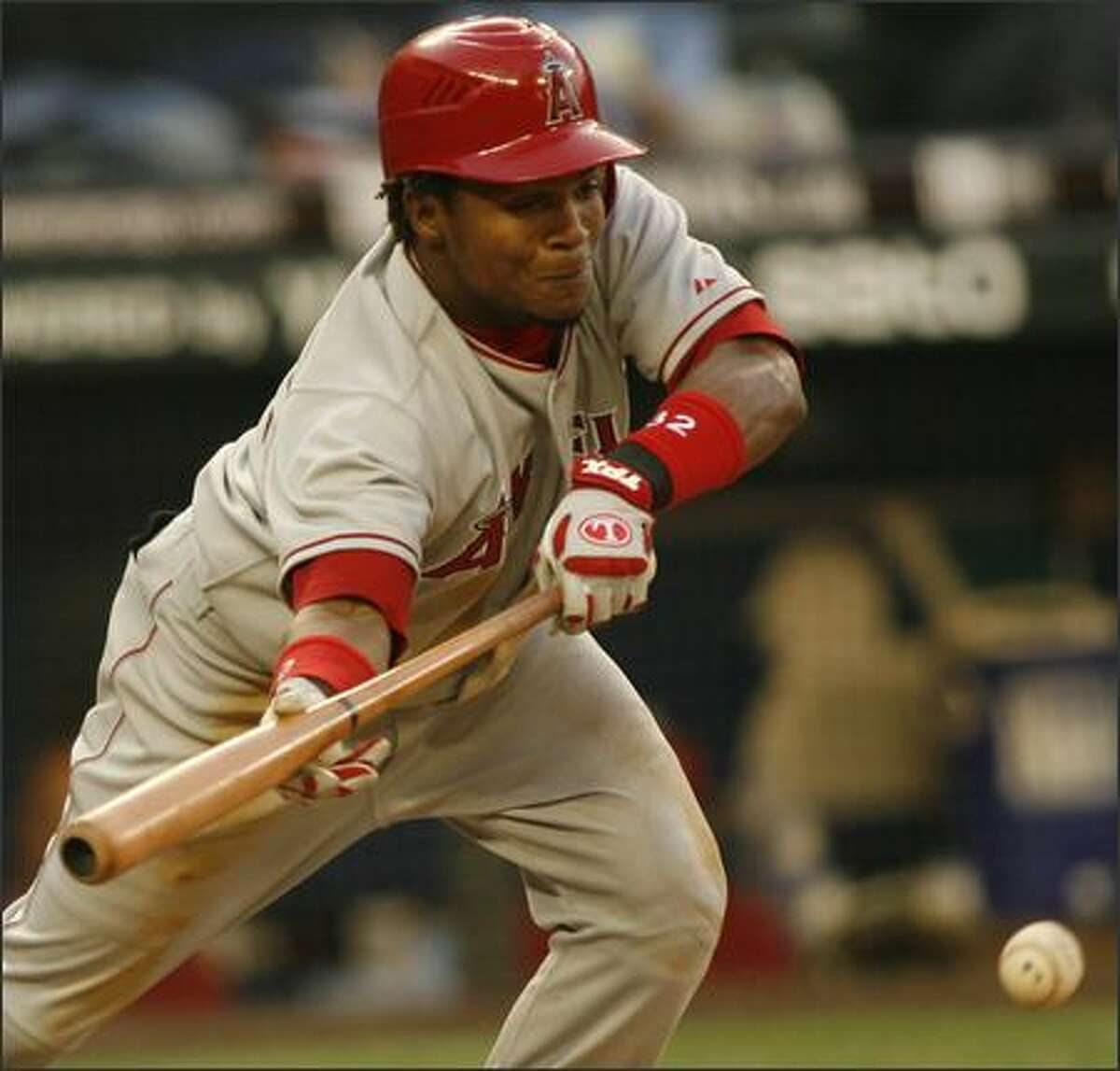 Los Angeles' Erick Aybar drops a sacrifice bunt in the fourth inning.