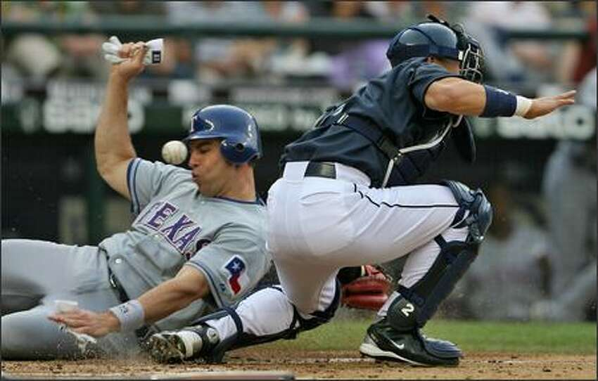 Seattle Mariners Kenji Jojima misses the ball as Texas Rangers Mark Teixeira slides into home to score on a Marlon Byrd single during third inning action at Safeco Field.