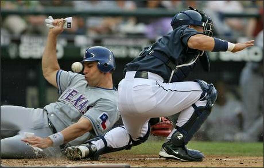 Seattle Mariners Kenji Jojima misses the ball as Texas Rangers Mark Teixeira slides into home to score on a Marlon Byrd single during third inning action at Safeco Field. Photo: Mike Urban, Seattle Post-Intelligencer / Seattle Post-Intelligencer